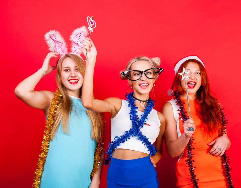 Młode dziwczyny bawiące się fotolustrem na imprezie
